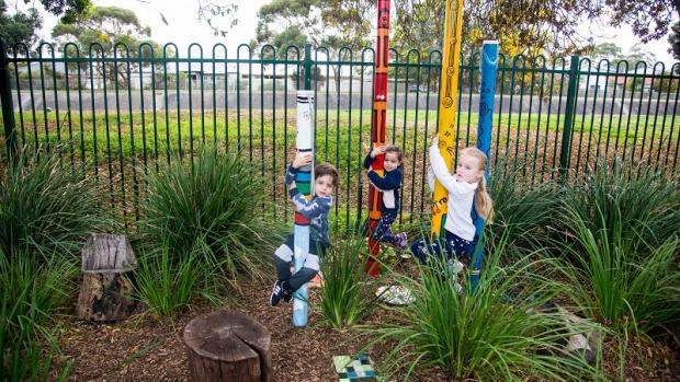 Photo of a boy and two girls climbing poles at kindy among strappy grasses