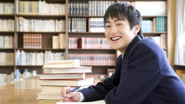 Male high school student of Asian appearance sitting at desk in library working