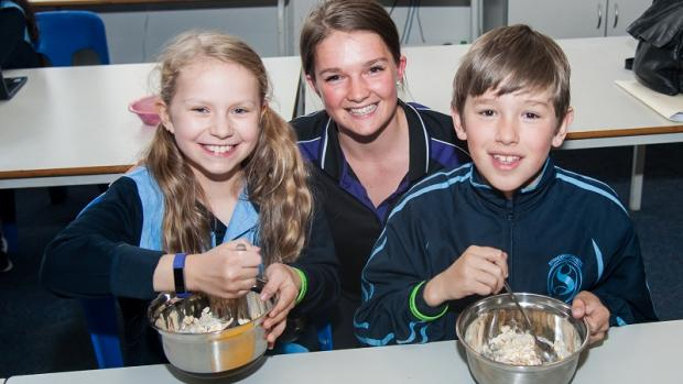 Girl, boy and educator do some cooking at out of school hours care