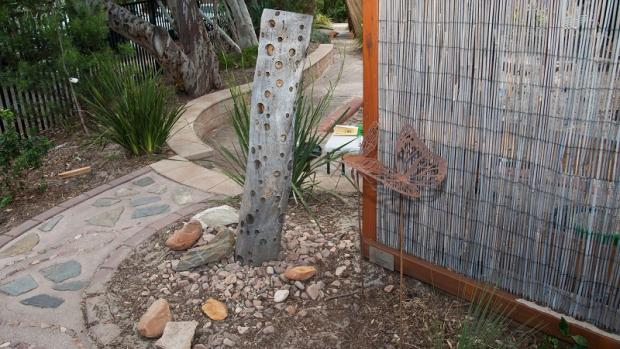 Outdoor space at a preschool showing a stone path, vertical log and metal butterfly sculpture next to a brushwood fence