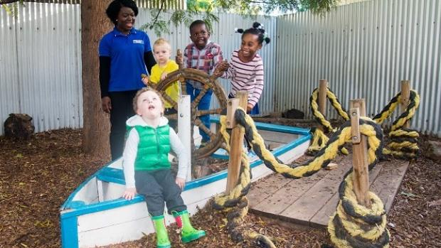 Educator supervises four children playing outside on a boat at a childcare centre
