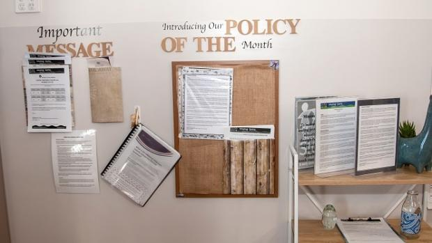 Pin board at education and care service with 'Introducing the policy of the month' on it