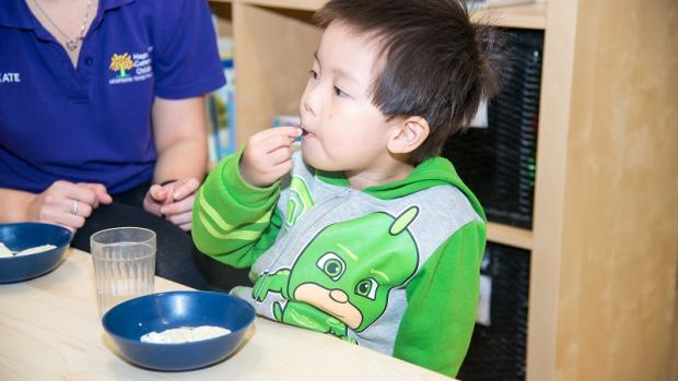 Preschool boy eating snacks at child-care centre with educator close by