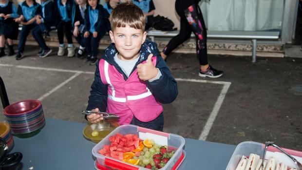 Preschool boy giving a thumbs up while helping himself to fruit at out of school hours care