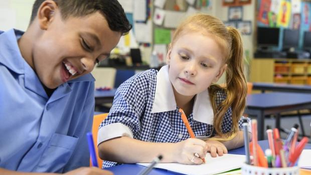 Primary school boy and girl at a school desk writing