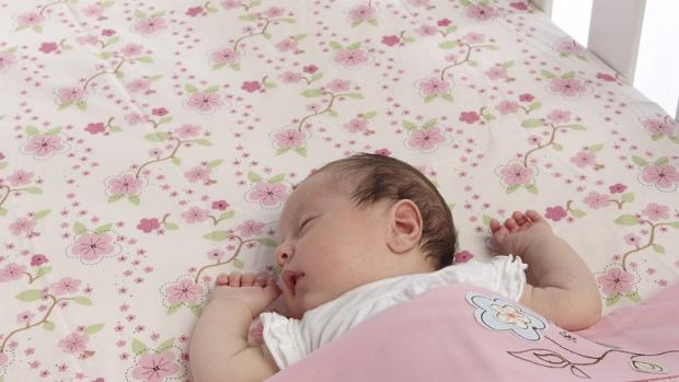 Baby girl sleeping safely at bottom of cot on back