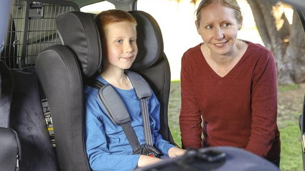 Eight-year-old boy in booster seat in car with his mum standing next to him