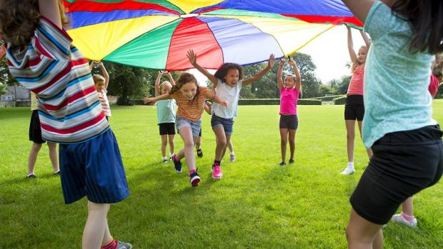 Primary school children wearing short and t-shirts playing with a parachute on grasson a