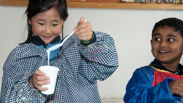Girl at out-of-school-hours care making slime, as boy watches her