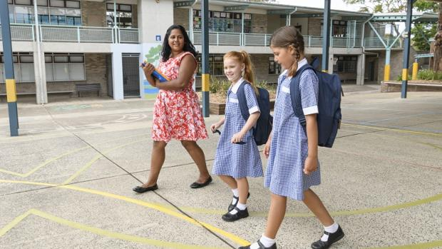 Teacher with two female students wearing uniforms walking together across a quadrangel