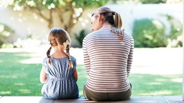 Young girl sitting with supportive woman, both facing away from our view