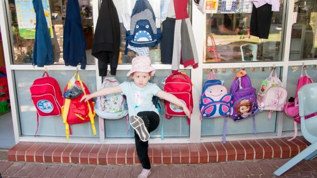 Preschool girl with outstretched arms and one leg in the air, in front of colourful bags and jackets on hooks